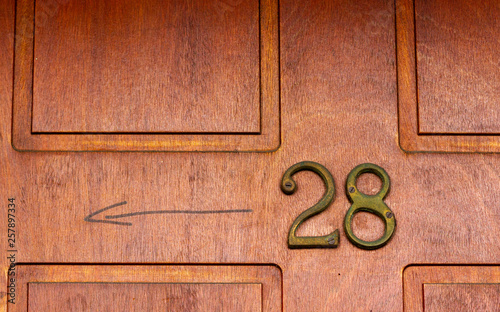 Fotografia  House number 28 with the twenty-eight in bronze metal on a natural grain wooden