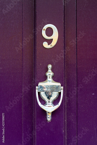 Fotografia  House number nine with the 9 in elegant curved design on a purple house door wit