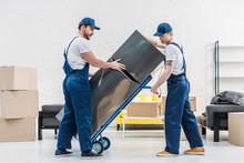 Two Movers Using Hand Truck Wh...
