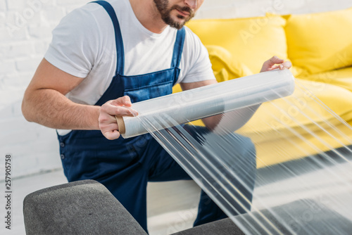 cropped view of mover wrapping furniture with roll of stretch film in apartment Canvas Print