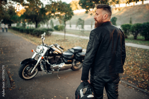 Fotografia, Obraz Bearded biker with helmet goes to his chopper