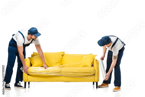 two movers wrapping yellow sofa with roll of stretch film on white