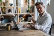 Portrait of businessman using laptop at desk