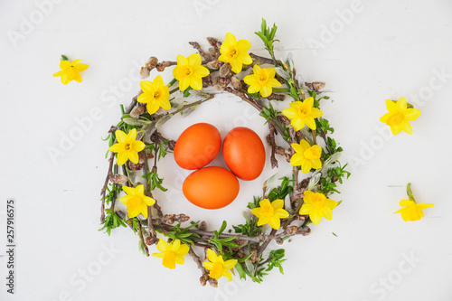 Self-made Easter wreath and orange dyed eggs on white ground