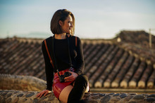 Young Woman Wearing Red Mini Skirt Sitting On A Wall Watching Sunset