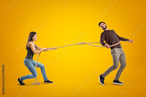Valokuvatapetti Side view of young woman lassooing young man on yellow background