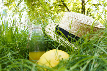 A straw hat is lying on the grass outdoors with a yellow citrus fruit and a bottle of lemonade. Picnic on nature in the park on a background of trees with bright sunshine