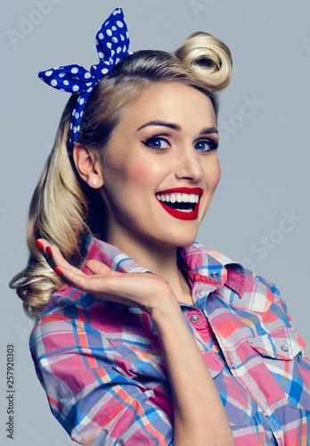 kobieta, ubrana w stylu pin-up, pokazując coś lub copyspace