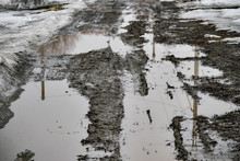 Broken Country Road With Mud And Puddles