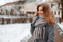 Fashionable Pretty Young Woman With A Beautiful Smile In A Gray Elegant Coat In A Stylish Gray Scarf In Gloves Walking Around The City Near Vintage Buildings. Attractive Girl Positive Enjoy The Walk.