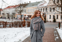 Urban Pretty Young Woman With A Beautiful Smile In A Gray Stylish Coat In A Knitted Warm Scarf Walks Around The City Near The Vintage Buildings On A Winter Day. Attractive Happy Girl On Vacation.