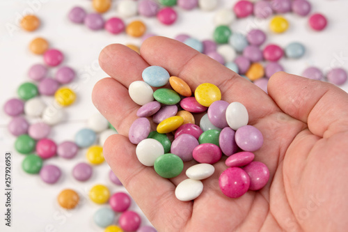 Round Colorful Chocolate Candys in the hand above blurred background (Flip 2019) Flip 2019