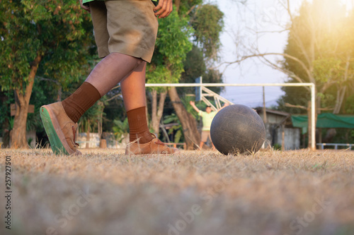 Fényképezés  A Boy kicking soccer ball on sports field