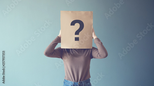 Fotografering Young girl has Confused, Thinking, Question Mark Icon on Paper Bag, copy space