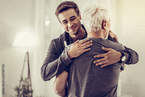 Smiling handsome young man embracing grey-haired dad cheering him up Poster Mural XXL