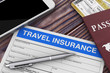 Travel Insurance Form near Mobile Phone, Passport and Air Tickets on a Wooden Table. 3d Rendering