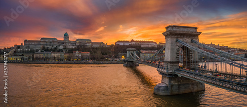 Budapest, Hungary - Aerial panoramic view of Szechenyi Chain Bridge with Buda Tunnel and Buda Castle Royal Palace at background with a dramatic colorful sunset #257944717