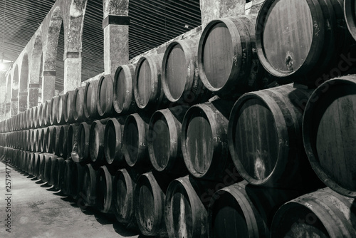 Fotografie, Obraz Barrels for whiskey or wine stacked in the cellar