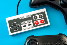 Computer Games And Gaming Console Concept Theme With Full Frame Of Video Game Controllers Isolated On Blue Background
