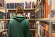 mężczyzna wybierający książkę w bibliotece
