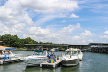 Luxury Speedboats Fueling Up At Gas Pump At Marina On Lake With Docks And Boats Behind Under Beautiful Blue Cloudy Sky