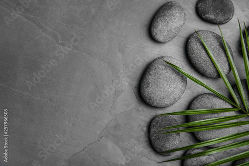 Zen stones and tropical leaf on dark background, top view with space for text - 257966508