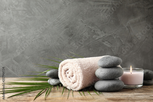La pose en embrasure Zen Composition with zen stones, towel and candle on table against grey background. Space for text