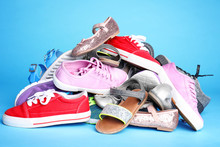 Heap Of Different Shoes On Color Background
