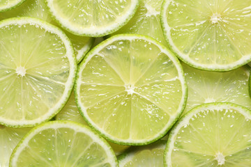 Juicy lime slices as background, top view. Citrus fruit