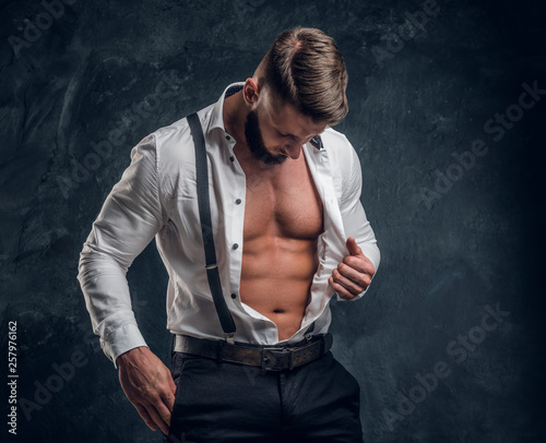 A stylish young man with a muscular body in the unbuttoned white shirt with suspenders. Studio photo against a dark wall background Wall mural