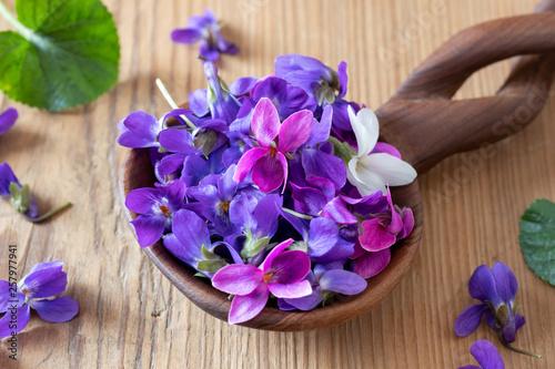 Wood violet flowers on a spoon on a table Fototapeta