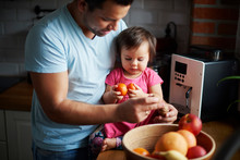 Father And Baby Girl Eating Fruit In Kitchen At Home