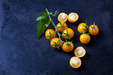 Whole And Sliced Cherry Tomatoes 'Golden Nugget' On Dark Ground