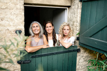 Portrait Of Three Smiling Women Of Different Age Behind Stable Gate