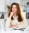 Portrait of young office woman who is working with laptop