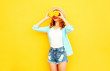 Leinwandbild Motiv Summer portrait happy smiling woman holding in her hands slices of orange hiding her eyes in straw hat, shorts on colorful yellow background