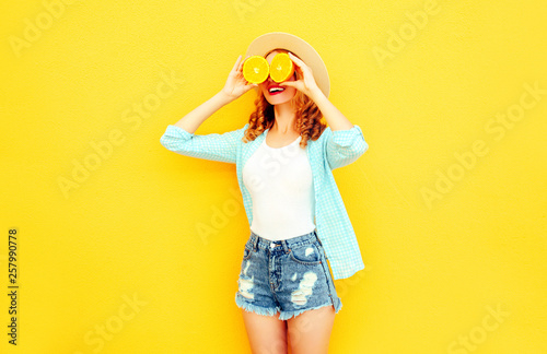 Summer portrait happy smiling woman holding in her hands slices of orange hiding her eyes in straw hat, shorts on colorful yellow background