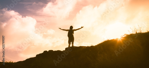 Fotografia  silhouette of a man on top of the mountain with arms outstretched