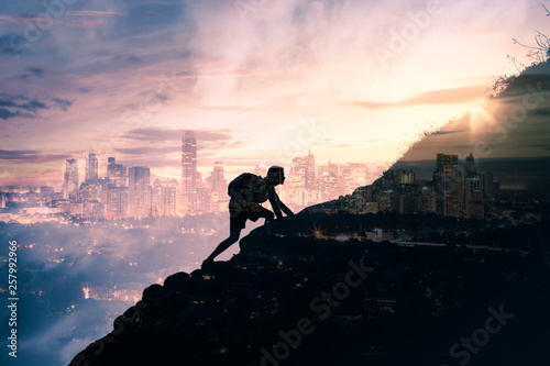 Fotografía  silhouette of man climbing up mountain overlooking city