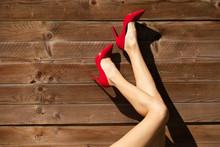 Female's Legs Posing In Red High Heels.