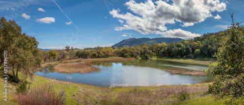 Fotografie, Obraz  A panoramic of a large pond reflecting clouds and sky