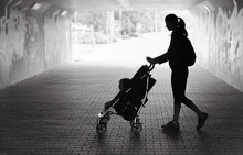 Single Mother Walking In City Tunnel Baby In Stroller. People Dark Sad Setting.