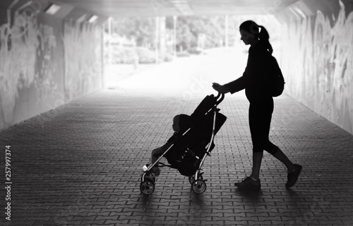 Photo Single mother walking in city tunnel baby in stroller