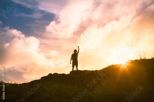 Victory, triumph, silhouette of man on top of mountain at sunset Canvas Print