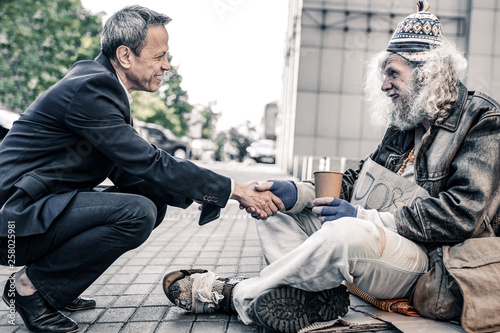 Obraz na płótnie Curious short-haired businessman sitting in front of long-haired homeless