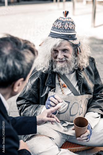 Rich man participating in act of charity while handing money to homeless Canvas Print