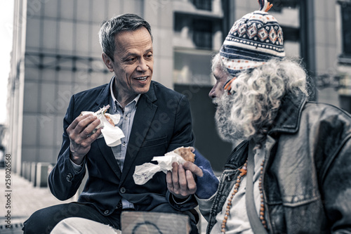 Communicative kind man talking to grey-haired senior homeless Canvas Print