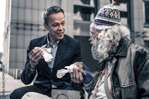 Communicative kind man talking to grey-haired senior homeless Fototapeta