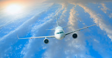White Passenger Airplane In The Clouds At Sunset - Travel By Air Transport