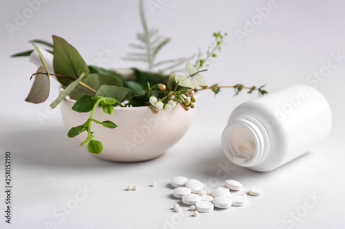 Bottle with pills and herbs on light background Canvas Print